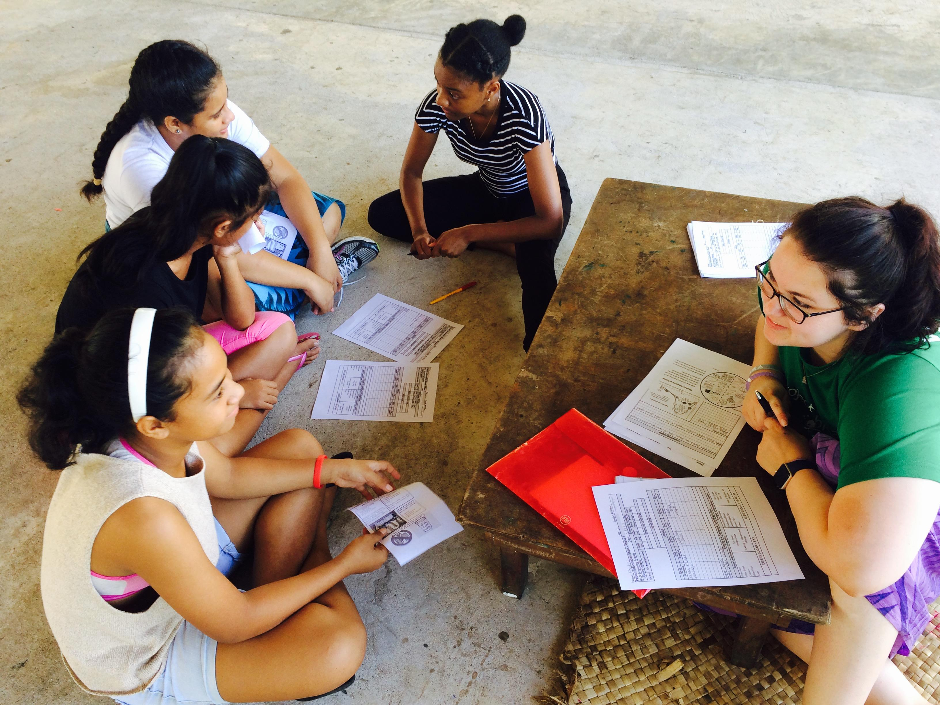 A student discusses healthy eating with local children during her Nutrition internship in Samoa.